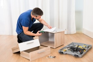 Portrait Of Carpenter Assembling Furniture At Home